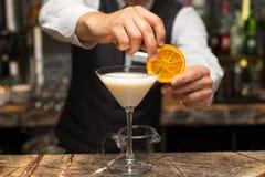 Bartender på arbete som förbereder coctailar hällande pinacolada till coctailexponeringsglas Royaltyfri Bild