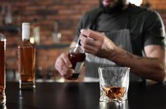 Bartender på räknaren med flaskor och exponeringsglas av whisky i stången, closeup royaltyfri bild