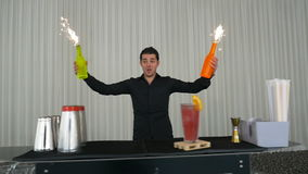 Bartender performing flair bartending with bottles and fireworks stock video footage