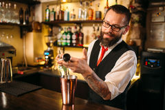 Bartender pouring alcohol beverage in metal glass Stock Image