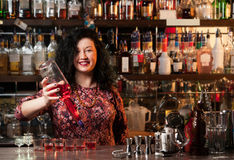 Bartender. Pouring alcohol into shot glasses Stock Images