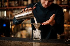 Bartender pouring an alcoholic cocktail into a cocktail glass from a steel shaker. Bartender pouring an alcoholic drink from the steel shaker into a cocktail royalty free stock photos