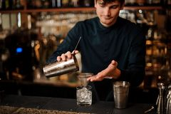 Bartender pouring an alcoholic cocktail into a glass from a steel shaker. Bartender pouring an alcoholic drink from a steel shaker into a cocktail glass with an royalty free stock images
