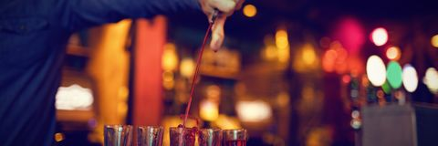 Bartender pouring alcoholic drink in shot glasses. At bar stock photo