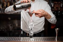 Bartender pouring an alcoholic drink from the steel shaker. Bartender pourring a red alcoholic drink from a steel shaker into a drink glass through a sieve on stock photography