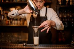 Bartender pouring an alcoholic drink from the steel shaker. Into a drink glass through the sieve on the bar counter royalty free stock photography