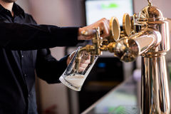 Bartender pouring beer from faucet in pint glass. Midsection of bartender pouring beer from faucet in pint glass at bar royalty free stock photos