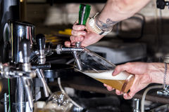 Bartender pouring beer. Into a glass from the tap Stock Photos