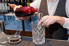 Bartender is pouring black currant shrub Stock Photo