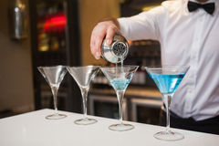 Bartender pouring blue alcohol into cocktail glass Stock Image