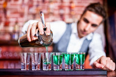 Bartender pouring blue curacao alcoholic cocktails. Bartender pouring blue curacao alcoholic cocktail in glasses on bar Stock Images
