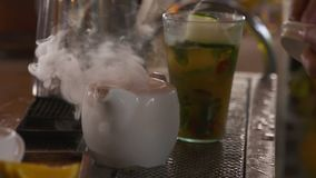 Putting boiling water, coke, and ice in a teapot. A bartender pouring boiling water, Coca-Cola, and ice into a teapot next to a cocktail glass stock video