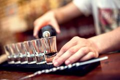 Bartender pouring brown alcoholic cocktail in glasses Royalty Free Stock Image