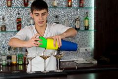Bartender pouring a cocktail. From a colourful cocktail shaker into three elegant glasses on the counter royalty free stock photos