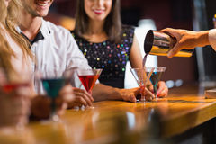 Bartender pouring cocktail for customers. At the nightclub stock image