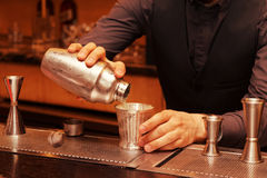Bartender is pouring cocktail into a glass, toned. Bartender is pouring cocktail from shaker into a glass, toned image royalty free stock photography