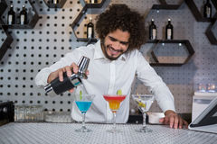 Bartender pouring cocktail into glasses. Bartender pouring cocktail from shaker into glasses at bar counter in bar stock images