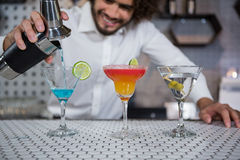 Bartender pouring cocktail into glasses. Bartender pouring cocktail from shaker into glasses at bar counter in bar royalty free stock photo