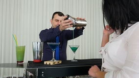Bartender pouring cocktail from shaker for girl at the bar stock video