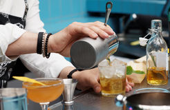 Bartender is pouring cocktail from shaker. Into the glass stock photos