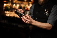 Bartender pouring cocktail with in a steel shaker. Close shot of bartender in gray shirt pouring alcohol cocktail with sour mix in a steel shaker stock images