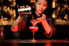 Bartender pouring cocktail using shaker and sieve highlighted in red. Cute female bartender pouring an alcohol cocktail using steel shaker and sieve at bar royalty free stock photo