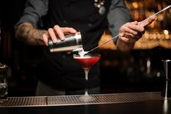 Bartender pouring cocktail using shaker and spoon. Brutal tattooed male bartender pouring red alcohol cocktail using steel shaker and long bar spoon at bar royalty free stock photo