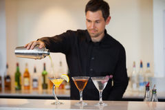 Bartender pouring cocktails Stock Images