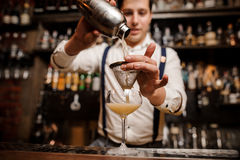 Bartender pouring coctail into the glass Royalty Free Stock Photos