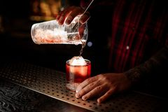 Bartender pouring a delicious Boulevardier cocktail from the measuring cup royalty free stock image