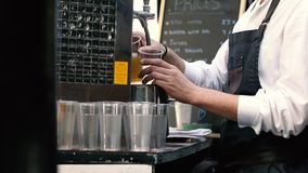 Bartender pouring draught beer. In plastic cups stock video