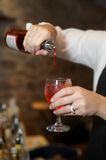 Bartender pouring drink. Bartender pouring bottle into red cosmopolitan mixed drink royalty free stock images