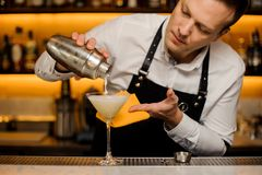 Bartender pouring a fresh alcoholic drink into the cocktail glass. Bartender pouring a fresh alcoholic drink into the elegant cocktail glass on the bar counter Stock Photo