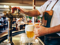 Bartender pouring the fresh beer in one of Czech traditional pub Stock Images