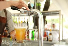 Bartender pouring fresh beer from tap, closeup stock images