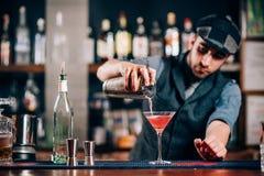 Barman pouring fresh cosmopolitan drink. Bartender pouring fresh cosmopolitan drink royalty free stock photo