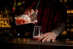 Bartender pouring fresh and tasty bittersweet red cocktail. Into an empty cocktail glass on bar stock photo
