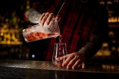 Bartender pouring fresh and tasty cool bittersweet red cocktail. Into an empty cocktail glass on bar royalty free stock image
