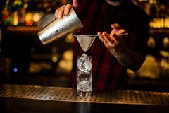Bartender pouring a Hurricane Punch cocktail from the steel shaker. On the bar counter on the blurred background stock image