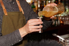 Bartender is pouring liquor in metal jigger Royalty Free Stock Photo