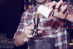 Bartender is pouring mango juice in jigger, toned Stock Photography