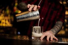 Bartender pouring a New York sour cocktail from the steel shaker. To a glass with big ice cube on the bar counter stock photography