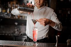 Bartender pouring a red alcoholic drink from the steel shaker. Bartender pourring a transparent red alcoholic drink from a steel shaker into a drink glass stock image