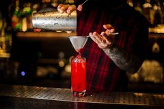 Bartender pouring red sweet juicy drink into a cocktail glass. Using a shaker and strainer royalty free stock images