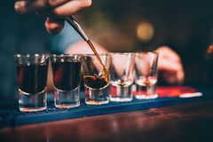 Bartender pouring and serving alcoholic drinks at bar Stock Photo