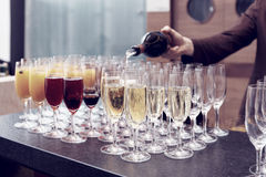 Bartender is pouring sparkling wine in glasses, toned image Royalty Free Stock Photo