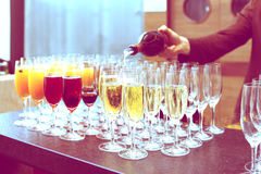 Bartender is pouring sparkling wine in glasses, toned Royalty Free Stock Photos