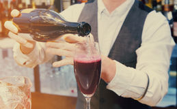 Bartender is pouring sparkling wine, toned Royalty Free Stock Photography