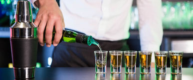 Bartender pouring tequila into shot glasses Royalty Free Stock Photo