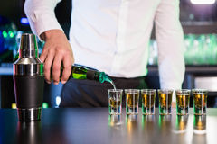 Bartender pouring tequila into shot glasses Stock Photos